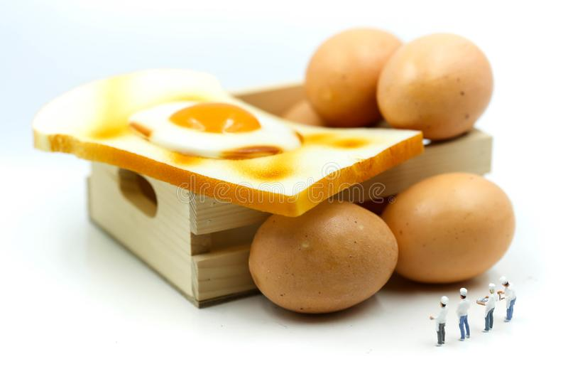 Miniature people : Chef cooking with Eggs for Breakfast with toast. stock photography