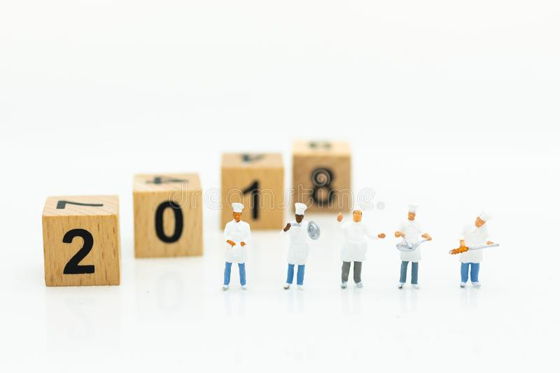 Miniature people: Chef standing with wooden block 2018. Image use for create idea for food production of the year.  stock photography