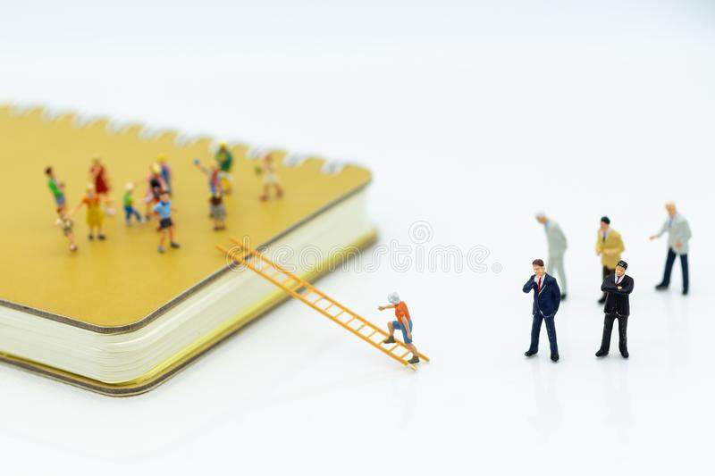 Miniature people: Child support and scholarships for underprivileged children. Image use for education concept.  stock photos