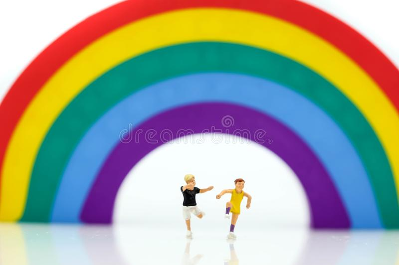 Miniature people : children cycling playground in city park with. Rainbow background,Play and learn concept stock images