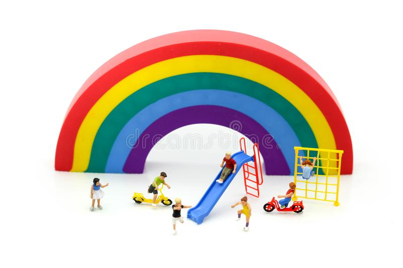 Miniature people : children cycling playground in city park with. Rainbow background,Play and learn concept stock image