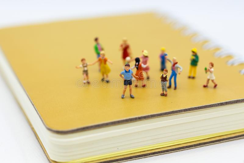Miniature people: Children group standing on book. Image use for learning together, education concept stock photography