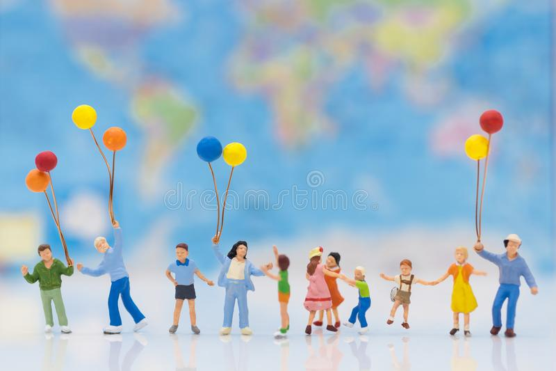 Miniature people: children hold balloons, and play together, background is map of world stock photo