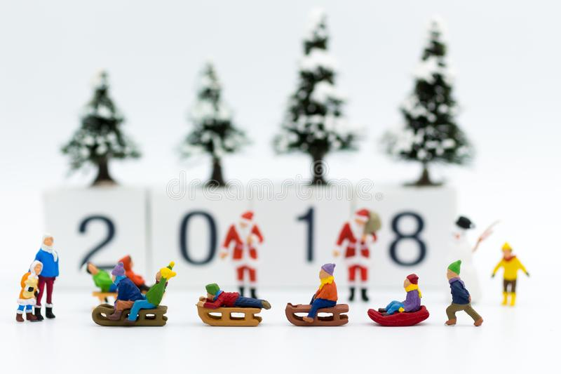 Miniature people: Children playing on snow funny together. Image use for Christmas festival. royalty free stock image