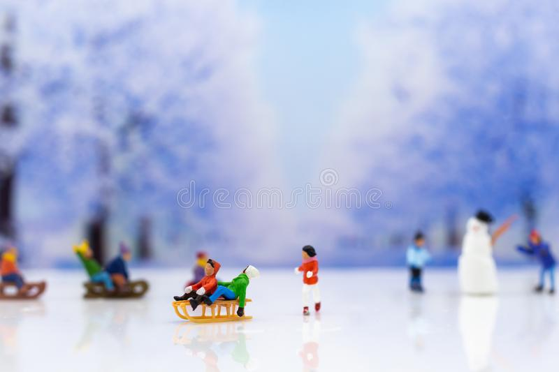 Miniature people: Children playing on snow funny together. Image use for Christmas festival. Miniature people: Children playing on snow funny together. Image stock image