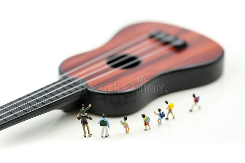 Miniature people : children and student with acoustic guitar,time of relax or music relax,stationary,education concept. stock photo