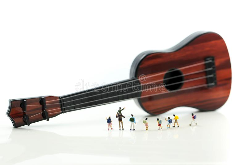 Miniature people : children and student with acoustic guitar,time of relax or music relax,stationary,education concept. stock photos