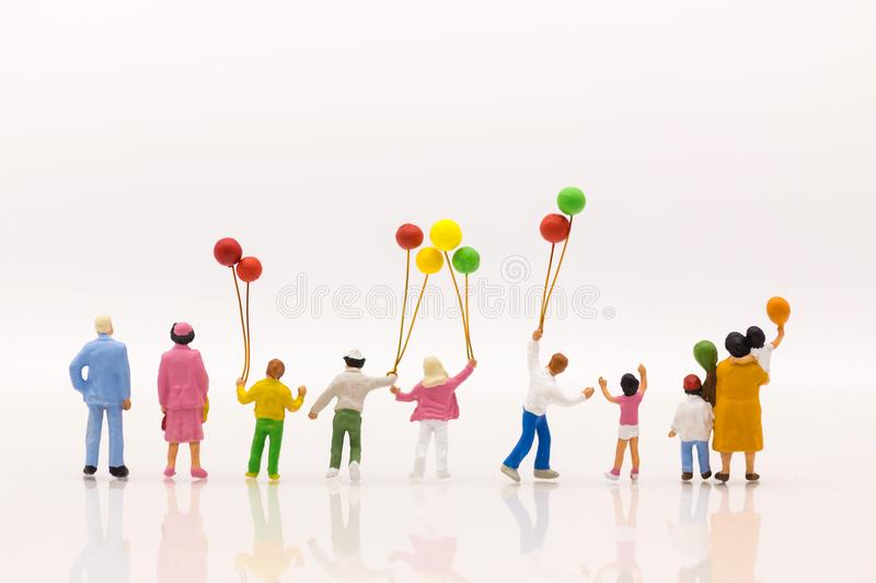 Miniature people: Childrens play balloon together wiht fun, using as background International day of families concept royalty free stock image