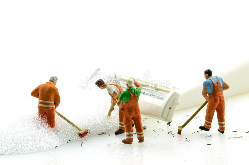 Miniature people cleaning dirty white shaver on white background royalty free stock photo