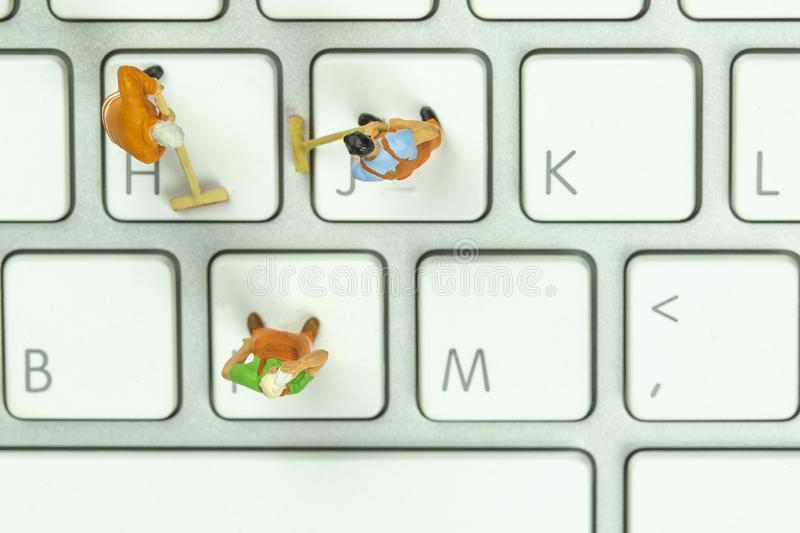 Miniature people cleaning white keyboard computer royalty free stock photography