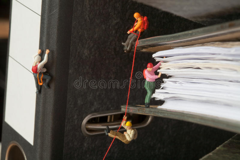 Miniature people climbing binders royalty free stock image