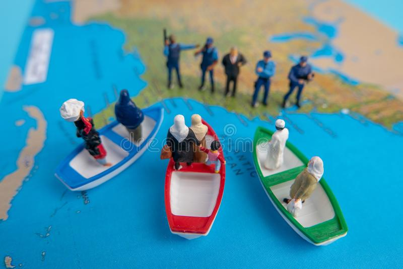 Miniature people concept of Middle Eastern people arrive by boat royalty free stock images