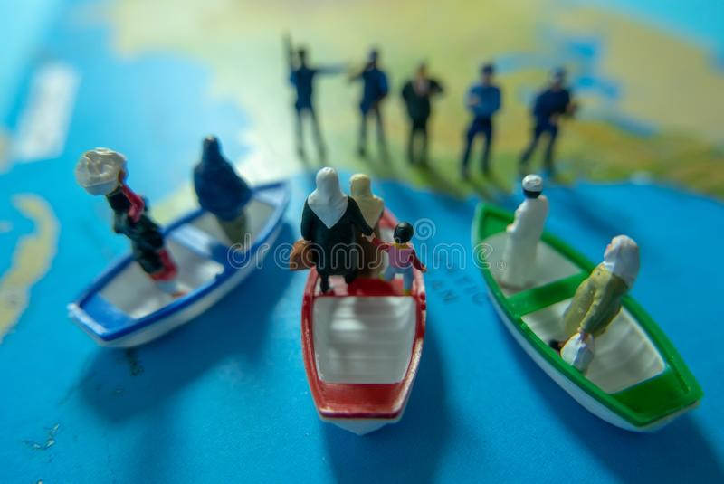 Miniature people concept of Middle Eastern people arrive by boat stock image