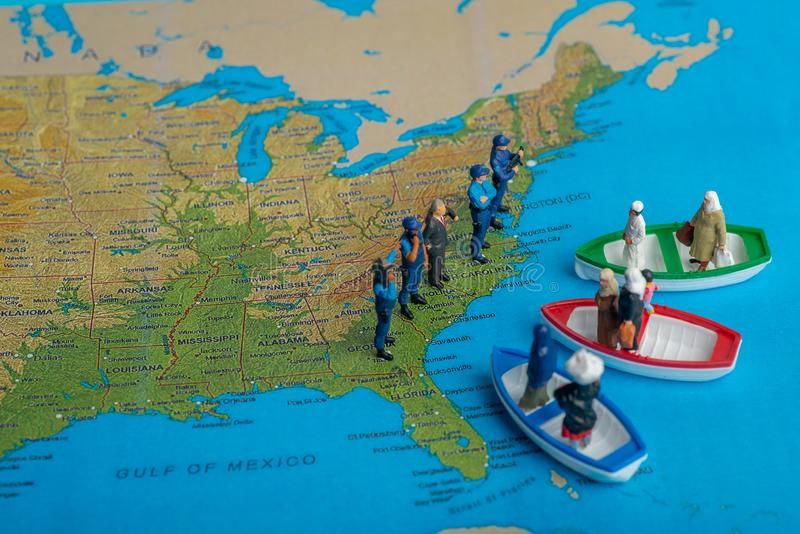 Miniature people concept of Middle Eastern people arrive by boat royalty free stock photo