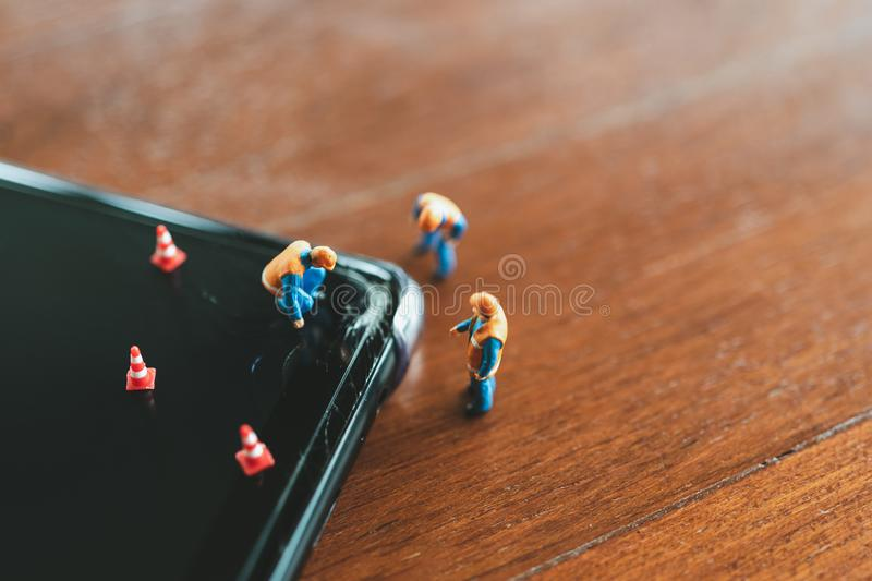 Miniature people Construction worker  repair smartphone using as background Maintenance concept and repair concept with copy space stock photo