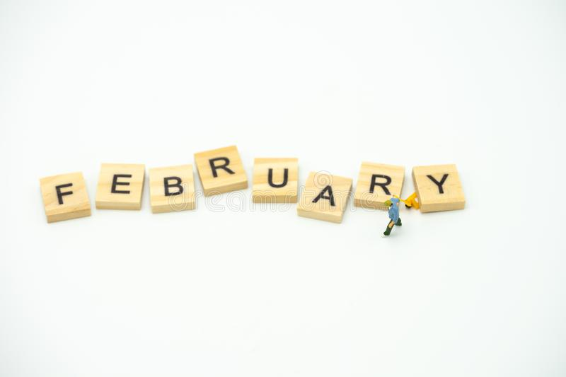 Miniature people Construction worker standing with wood word Month. using as background business concept and calendar concept with. Copy space for your text royalty free stock photography