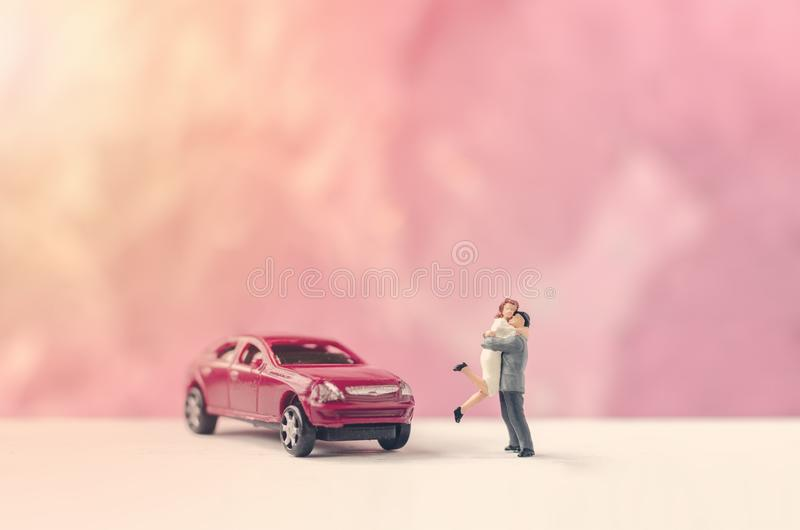 Miniature people couple lover hugging near car. Valentine day concept royalty free stock photography