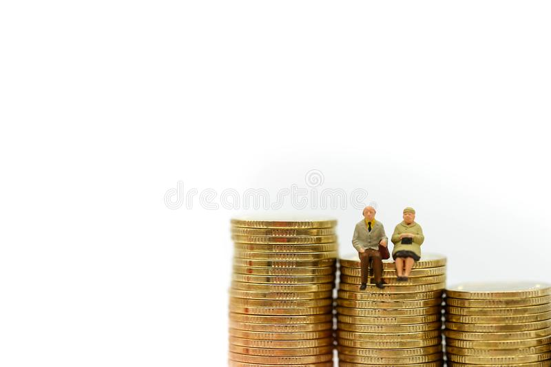 Miniature people : Couple oldman sitting with stack of coins,Business concept. stock photos