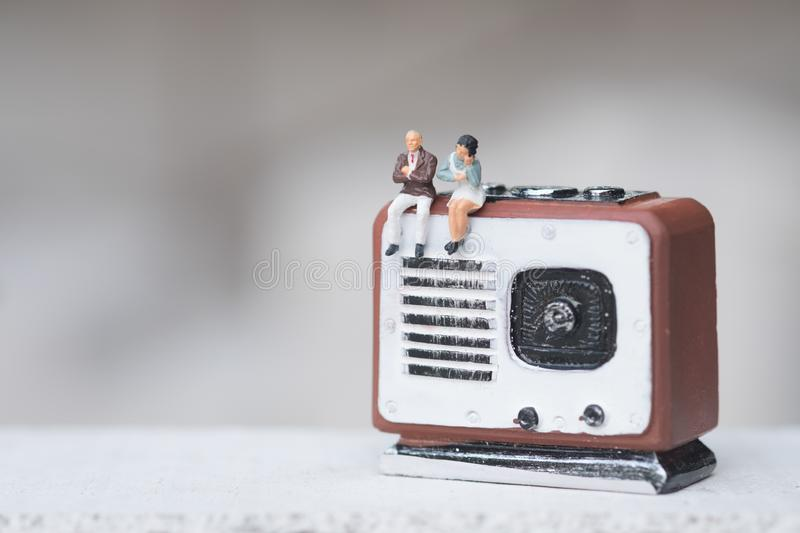 Miniature people couple sitting on radio retro. Concept of good old memories stock image