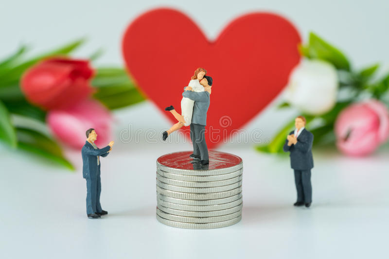 Miniature people with couple standing on top stack of coins and stock images