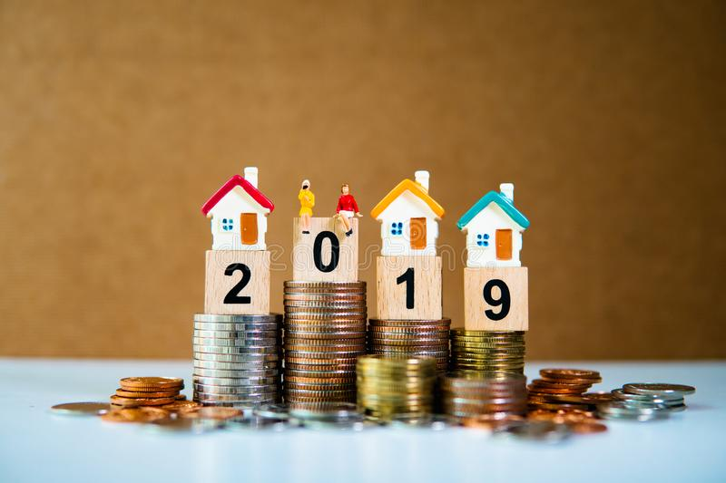 Miniature people, couple woman sitting on pile of coins. With house and wooden block year 2019 using as business and property concept stock photo
