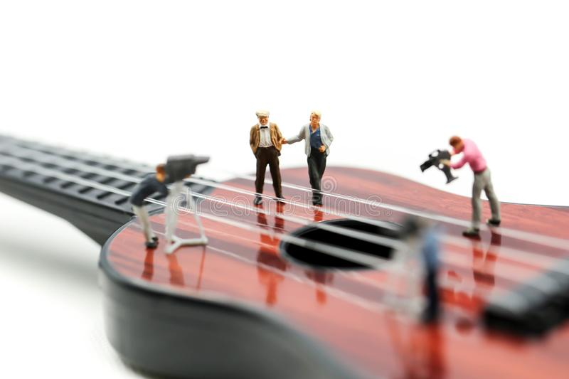 Miniature people : Director, staff and actors on the set of the video singer with guitar,production music concept.  stock image