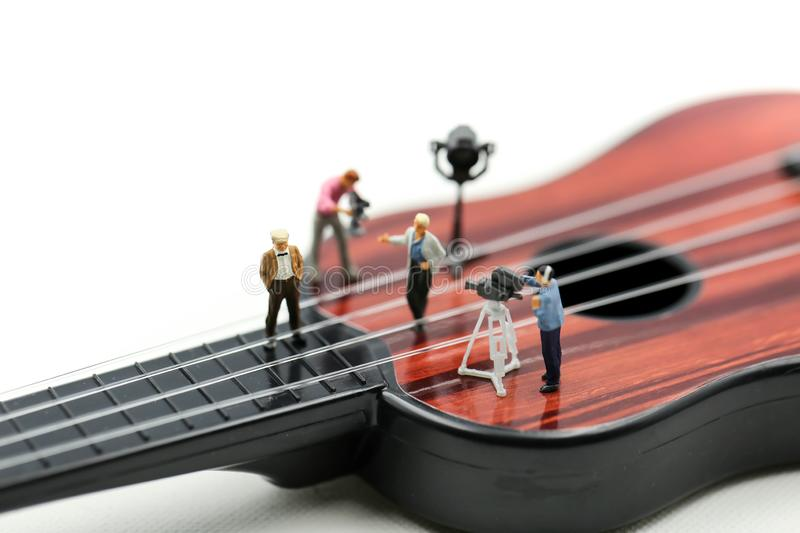 Miniature people : Director, staff and actors on the set of the video singer with guitar,production music concept.  royalty free stock image