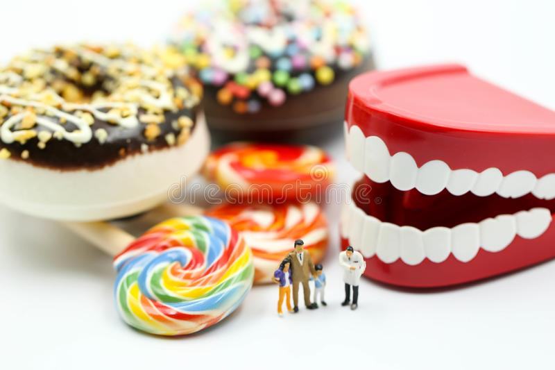 Miniature people : Doctor dentist speaks about student and children with desserts,Fun eating and healthcare  concept.  royalty free stock images
