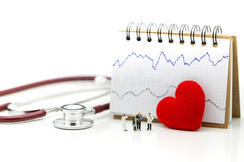 Miniature people : Doctor and patient Cardiogram with stethoscope and red heart,A heart beats graph concept. royalty free stock photography