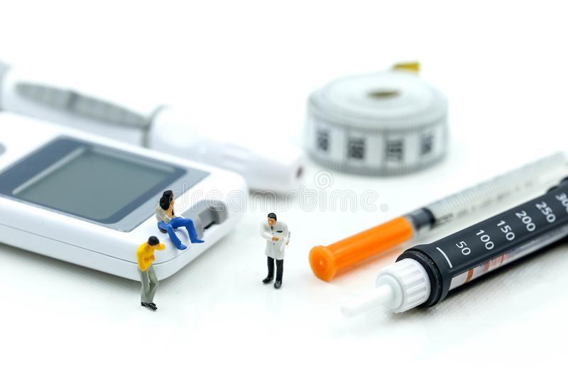 Miniature people : Doctor and Patient with Insulin pen ,Diabetes equipment ,glucose level blood test,Diabetes concept royalty free stock photography