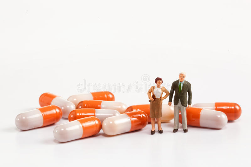 Miniature people - Elderly people posing in front of pills. On a white background stock photography