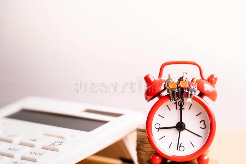 Miniature people: Elderly people sitting on red alarm clock. royalty free stock photos