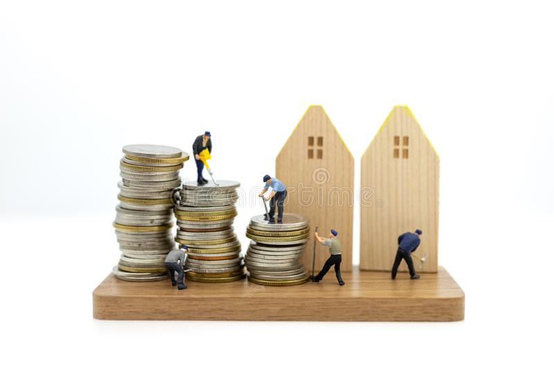 Miniature people: Employee standing on stack of coins with device for home design. Image use for Building, idea concept.  stock photos