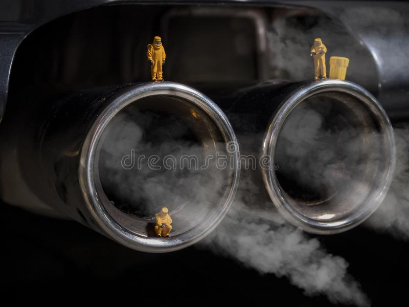 Miniature people examining car exhaust royalty free stock photography