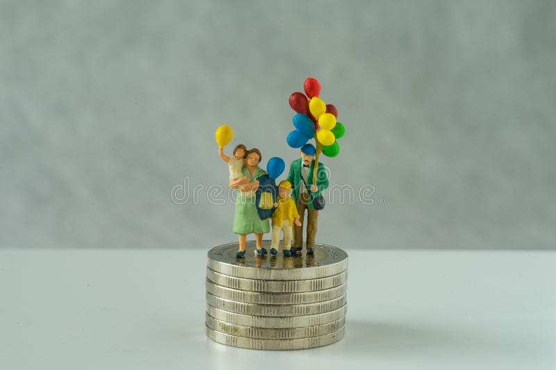 Miniature people, family holding balloon standing on stack of coins as financial business or happy retirement concept stock image