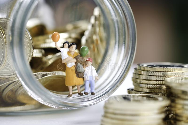 Miniature People : Family are standing on the glass jar full with coins use as saving , insurance and plan for the future. Miniature People : Family are standing stock photos