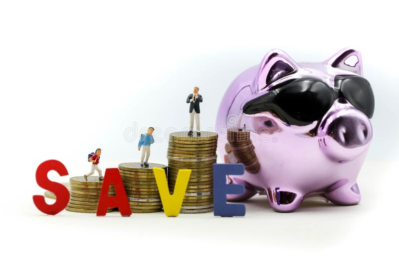 Miniature people : Family teach children saveing money coins with piggy bank,Teach your Children to save day.  royalty free stock photography