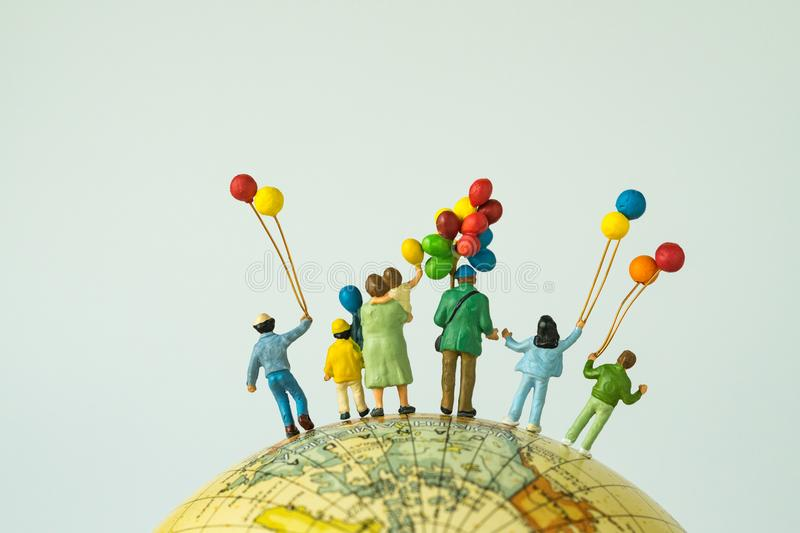 Miniature people figure back view of happy family holding balloons standing on globe as looking into the universe or happy. American family concept stock images