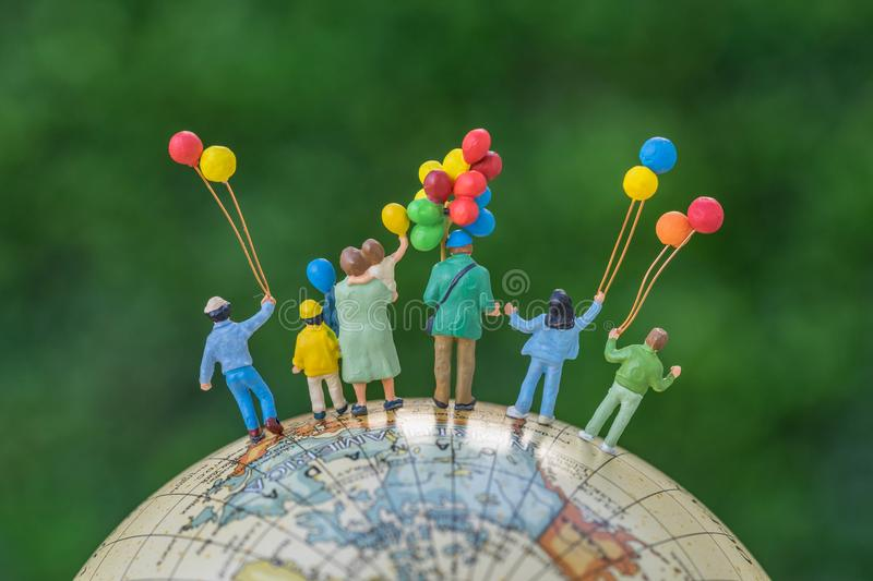 Miniature people figure back view of happy family holding balloons standing on globe as world climate change environment or happy. Family concept stock images