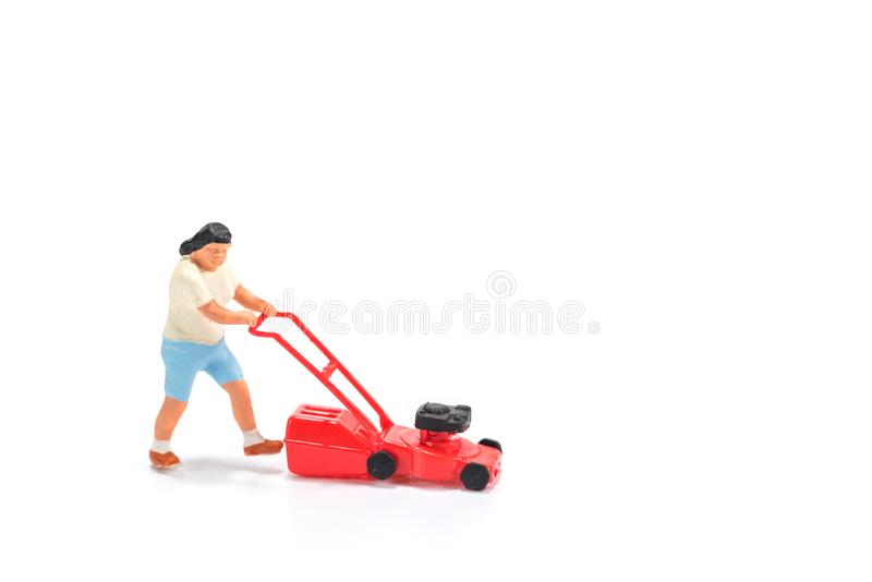 miniature people figure holding mower isolated on white background stock images