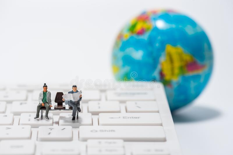 Miniature people figure sitting on bench with globe figure back royalty free stock photo