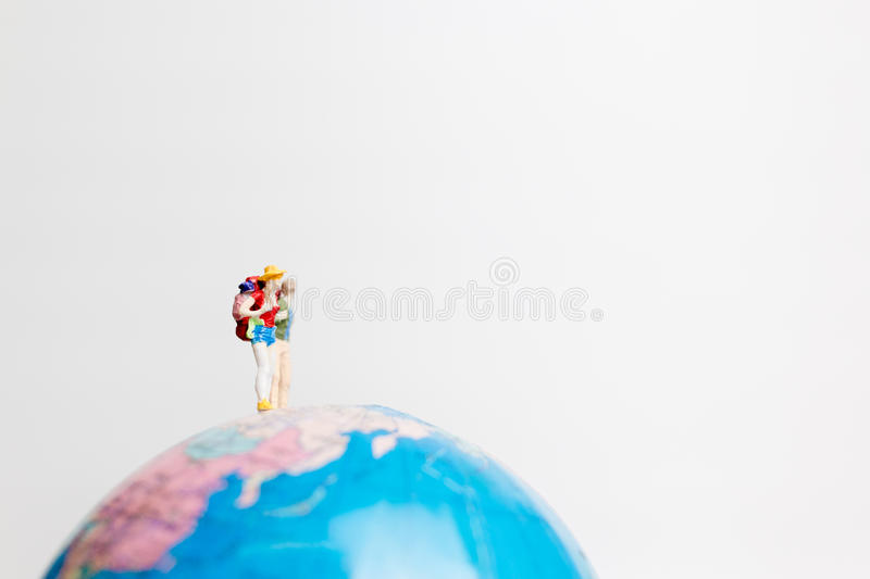 Miniature people figure standing on the globe world map. With white background and copy space as travel concept stock photo