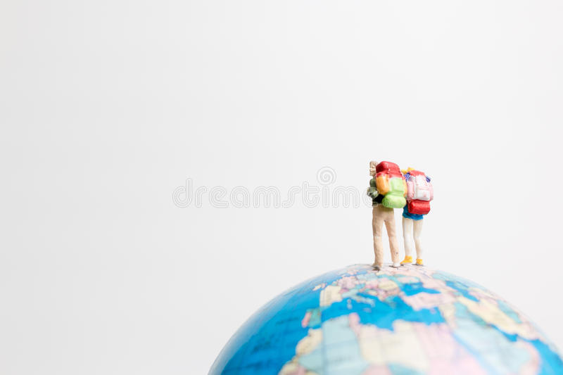 Miniature people figure standing on the globe world map. With white background and copy space as travel concept stock photography