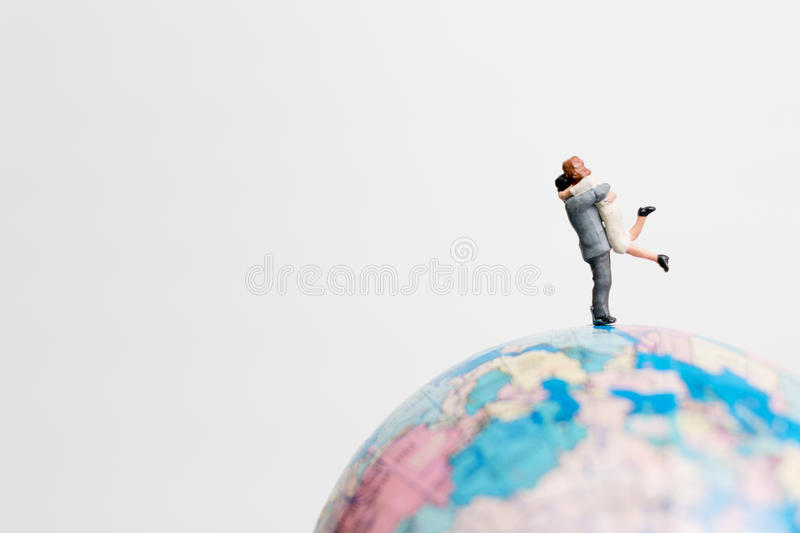 Miniature people figure standing on the globe world map. With white background and copy space as travel concept royalty free stock photos