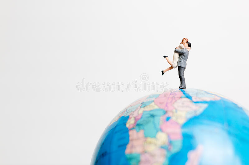 Miniature people figure standing on the globe world map. With white background and copy space as travel concept stock image