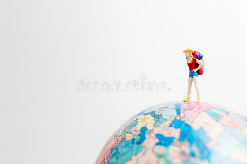Miniature people figure standing on the globe world map. With white background and copy space as travel concept royalty free stock image