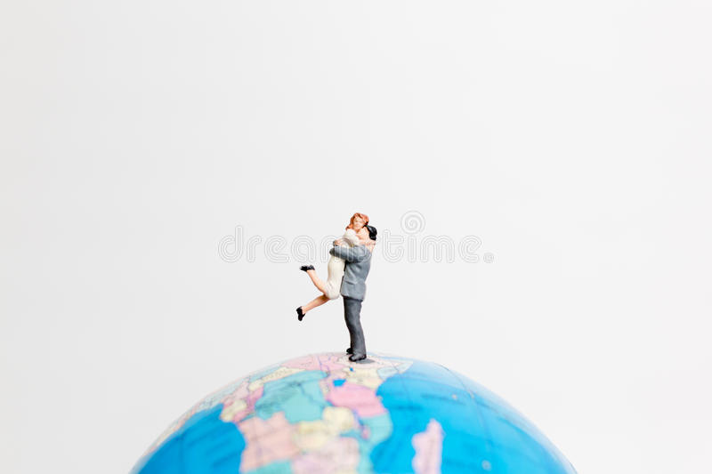 Miniature people figure standing on the globe world map. With white background and copy space as travel concept stock images