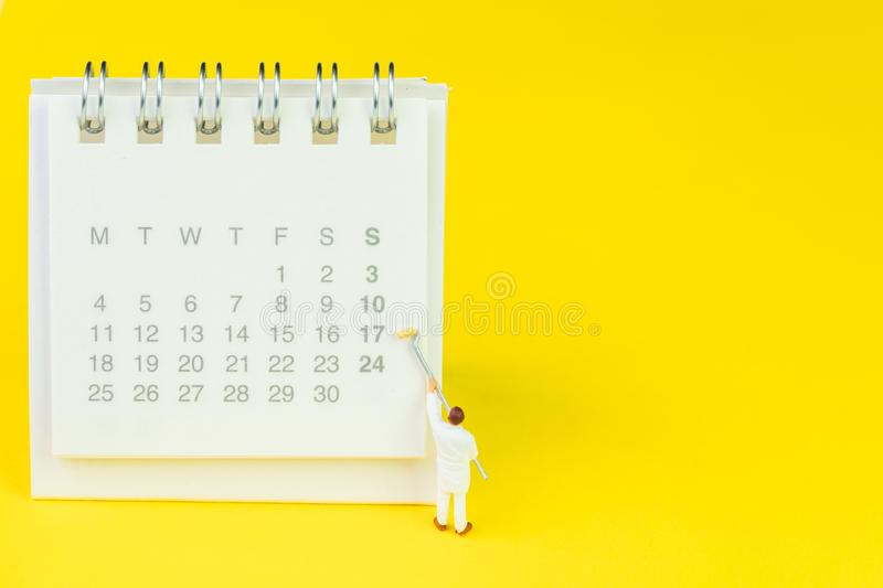 Miniature people figures using paint roller on white clean desktop calendar on solid yellow background with copy space, schedule stock image