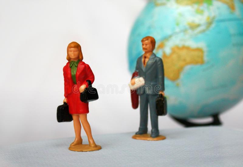 Miniature people and globe background. First mini lady figure and gentlemen behind her. Maybe marriage quarrel on the trip stock photo