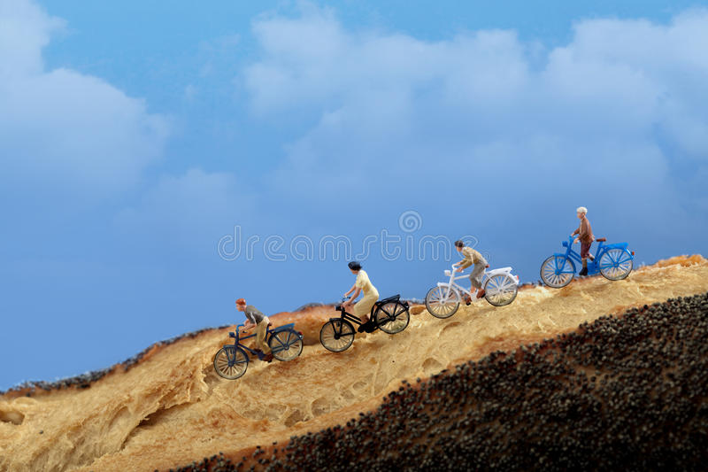 Miniature people: A group of cyclists enjoy rolling on a country road, royalty free stock images